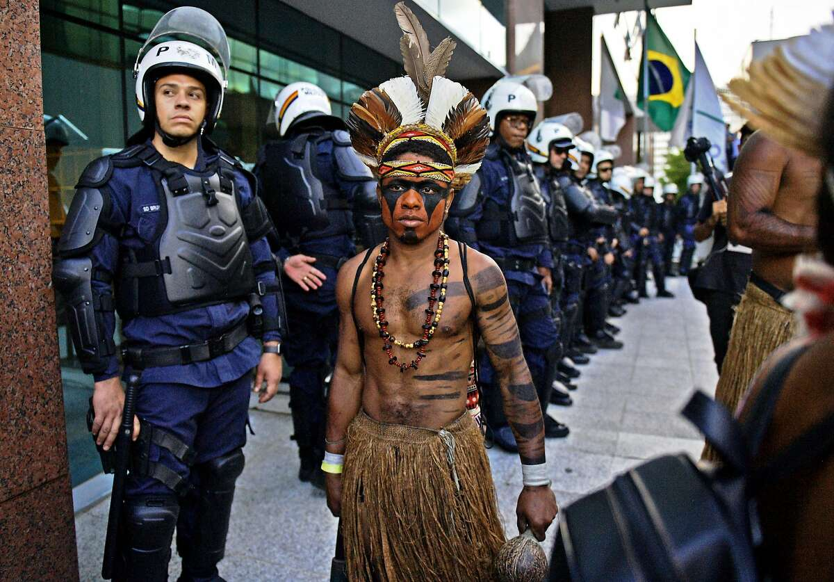 An indigenous man walks past riot police during a protest against the government's decision not to recognize the land demarcation of indigenous people living in Raposa Serra do Sol, Brazil, on April 25.
