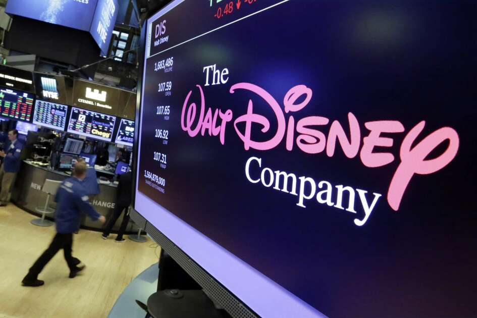In this Aug. 8, 2017, photo, The Walt Disney Co. logo appears on a screen above the floor of the New York Stock Exchange. Comcast Corp. made a long-awaited offer to acquire much of 21st Century Fox Inc., topping a previous proposal by Walt Disney Co. and setting up a bidding war for Rupert Murdoch's media empire.