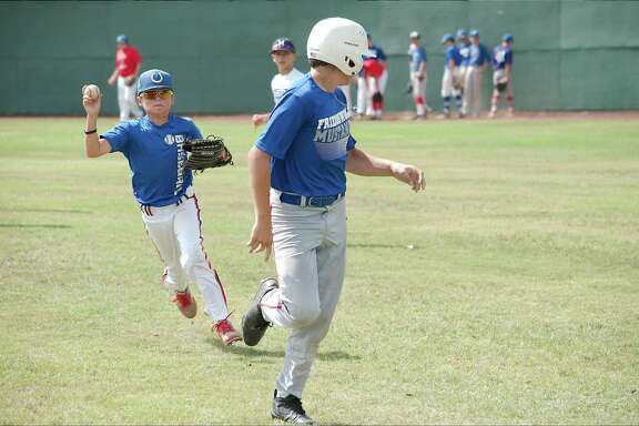 Drew Harris and Tatum Black participate in a run-down drill at the Friendswood summer baseball camp Tuesday, June 12.