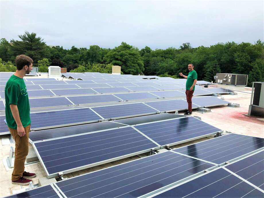 Daniel Scarozza of PurePoint Energy, right, with company intern Ben Eller on Wednesday, June 13, 2018, on a commercial rooftop at 110 Post Road in Darien, Conn. (Photo courtesy PurePoint Energy)
