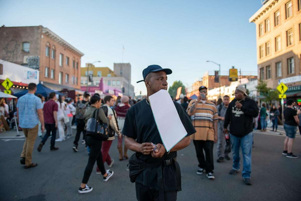 Max Gibson looks for places to put up posters promoting Feels 6 at Oakland�s First Friday on Friday, June 1, 2018.
