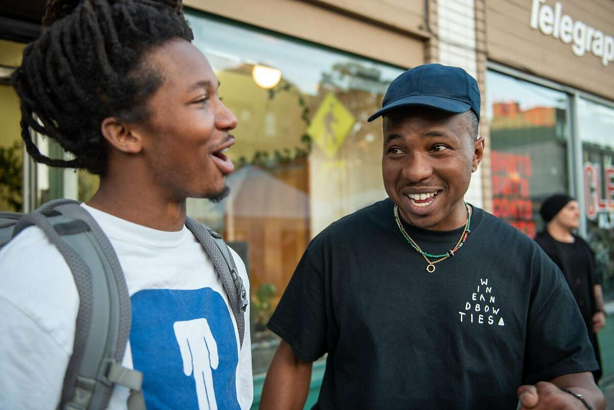 Max Gibson (right) greets his friend Malachi Knox while promoting Feels 6 at Oakland�s First Friday on Friday, June 1, 2018.