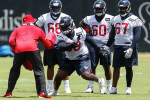 Houston Texans nose tackle D.J. Reader (98) runs a drill with defensive line coach Anthony Weaver during mini camp at The Methodist Training Center on Wednesday, June 13, 2018, in Houston.