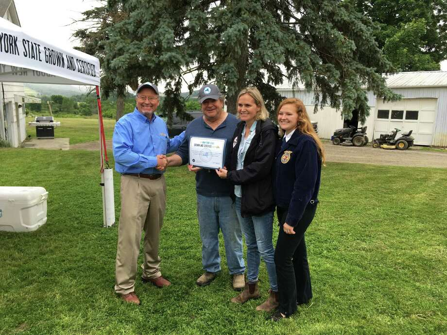 State Agriculture Commissioner Richard Ball, left, presentsRick Osofsky and his family, the owners of Ronnybrook FarmDairy, with their New York State Grown and Certified program certification on June 13, 2018. (Madison Iszler/Times Union)