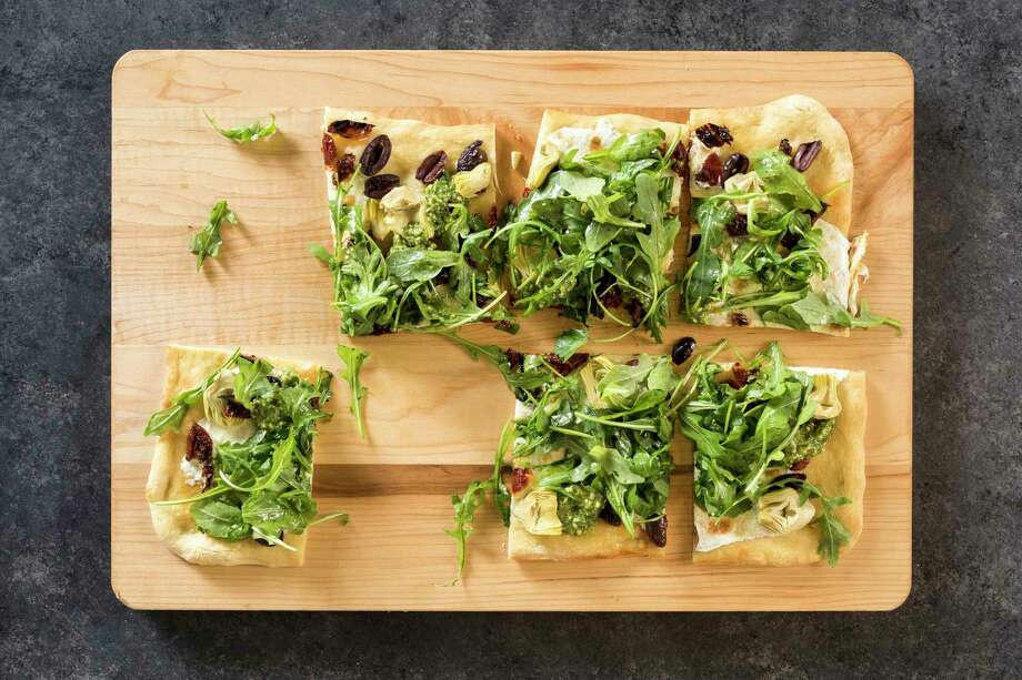 """This undated photo provided by America's Test Kitchen in May 2018 shows pesto flatbread with artichokes, olives and arugula in Brookline, Mass. This recipe appears in the cookbook """"Dinner Illustrated."""" (Daniel J. van Ackere/America's Test Kitchen via AP) Photo: Daniel J. Van Ackere / © 2017 America's Test Kitchen, LLC. All Rights Reserved."""