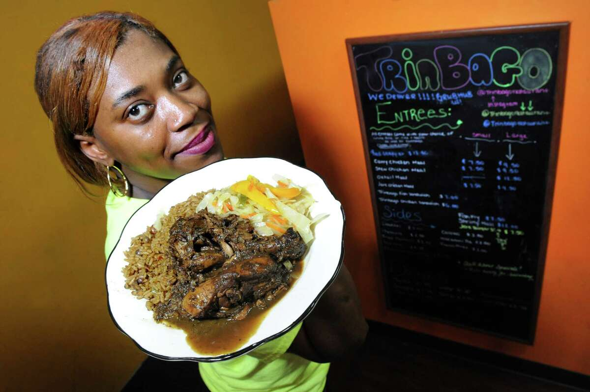 Owner and chef Nyota Haley holds a plate of Jerk Chicken on Tuesday, May 24, 2016, at Trinbago Caribbean Restaurant in Albany, N.Y. (Cindy Schultz / Times Union)