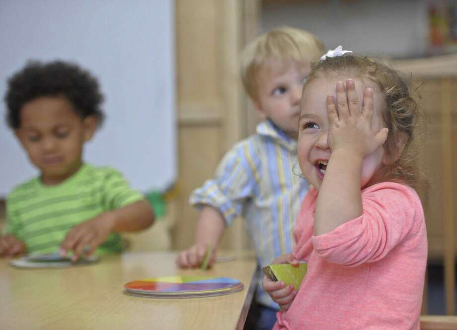 Penelope Vonderheide, 2, of Danbury, reacts to a playmate during the YMCA Grassy Plain Children's Center afternoon program in Bethel, Conn, Tuesday, June 12, 2018. Working on puzzels with Penelope are Luiemil Rodriguez, 2, of Bethel, left, and Maxwell Monteverde, 22 month, of Bethel. Photo: H John Voorhees III / Hearst Connecticut Media / The News-Times