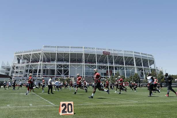 San Francisco 49ers players run on a practice field in front of Levi's Stadium during NFL football practice at the team's headquarters in Santa Clara, Calif., Wednesday, June 13, 2018. Year one under coach Kyle Shanahan was a bit of a whirlwind for the San Francisco 49ers with new systems to install and a midseason quarterback change to Jimmy Garoppolo. It's far different this year as the Niners wrap up the offseason program. (AP Photo/Jeff Chiu)