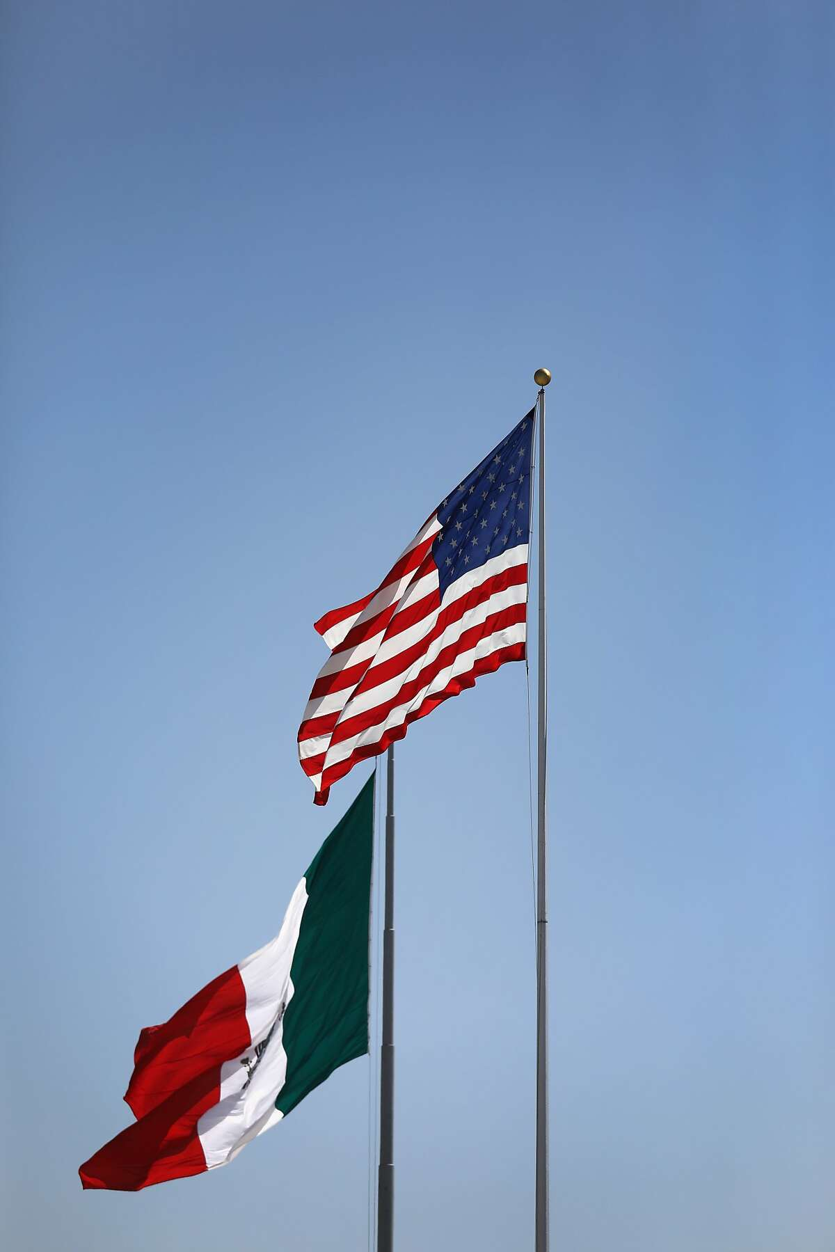 TIJUANA, MEXICO - SEPTEMBER 23: The American and Mexican flags stand on either side of the U.S.-Mexico border on September 23, 2016 in Tijuana, Mexico. Securing the border and controlling illegal immigration have become key issues in the U.S. Presidential campaign. (Photo by John Moore/Getty Images)
