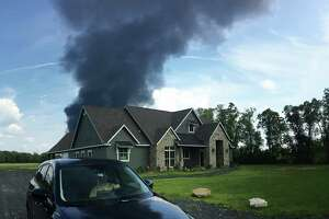 A plume of smoke from the Arkema plant in Crosby is seen blowing over a nearby home.