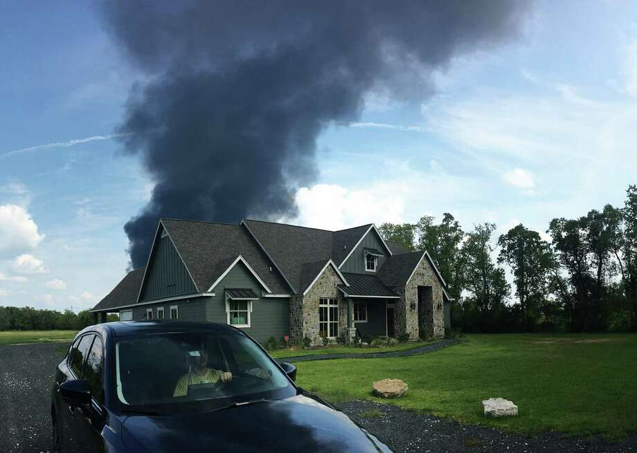 A plume of smoke from the Arkema plant in Crosby is seen blowing over a nearby home. Photo: Ethan Killion / Ethan Killion