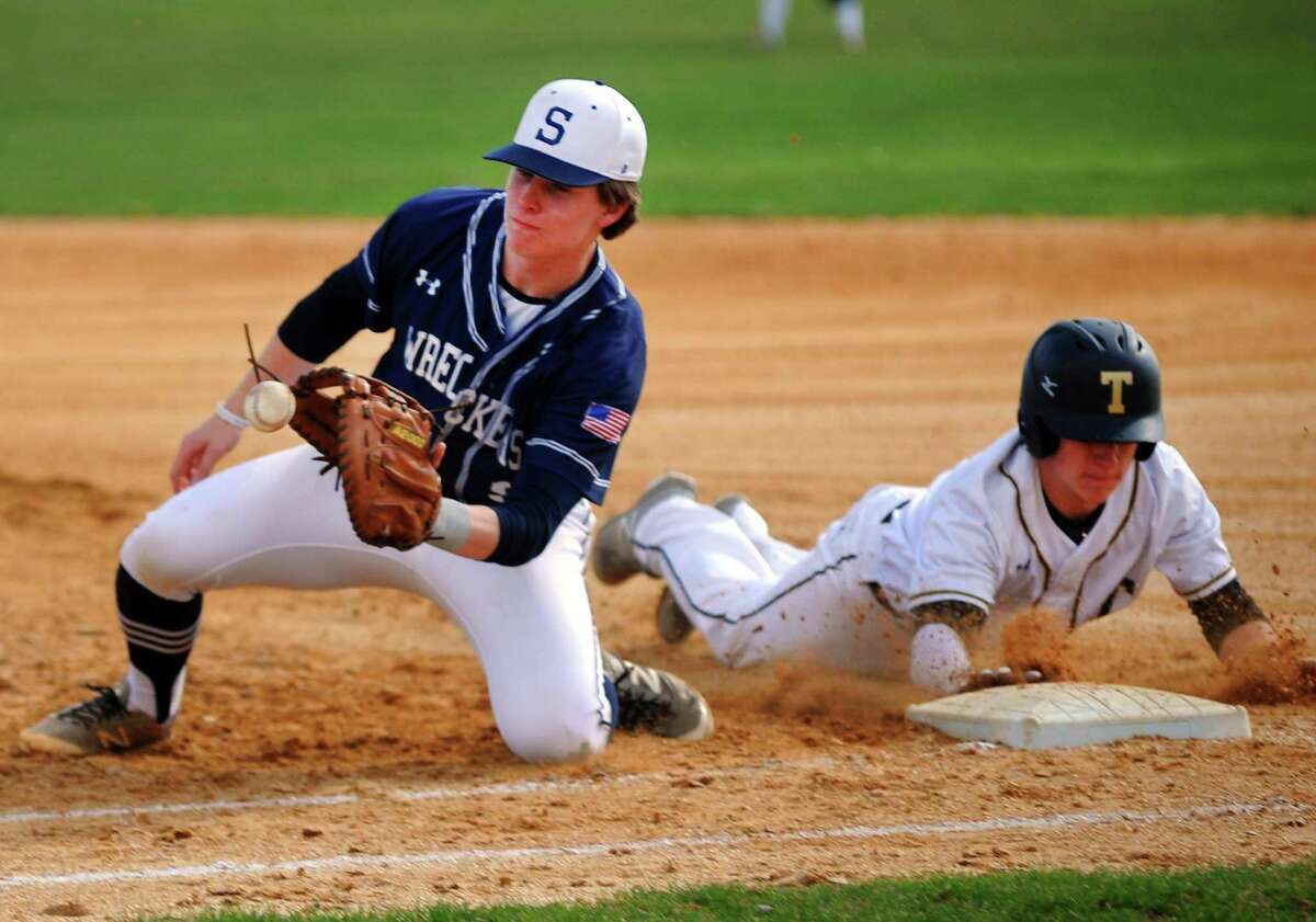 Staples' Harris Azadian receives the ball at first as Trumbull's Kevin Bruggeman dives back to first during boys baseball action in Trumbull, Conn., on Wednesday Apr. 18, 2018.