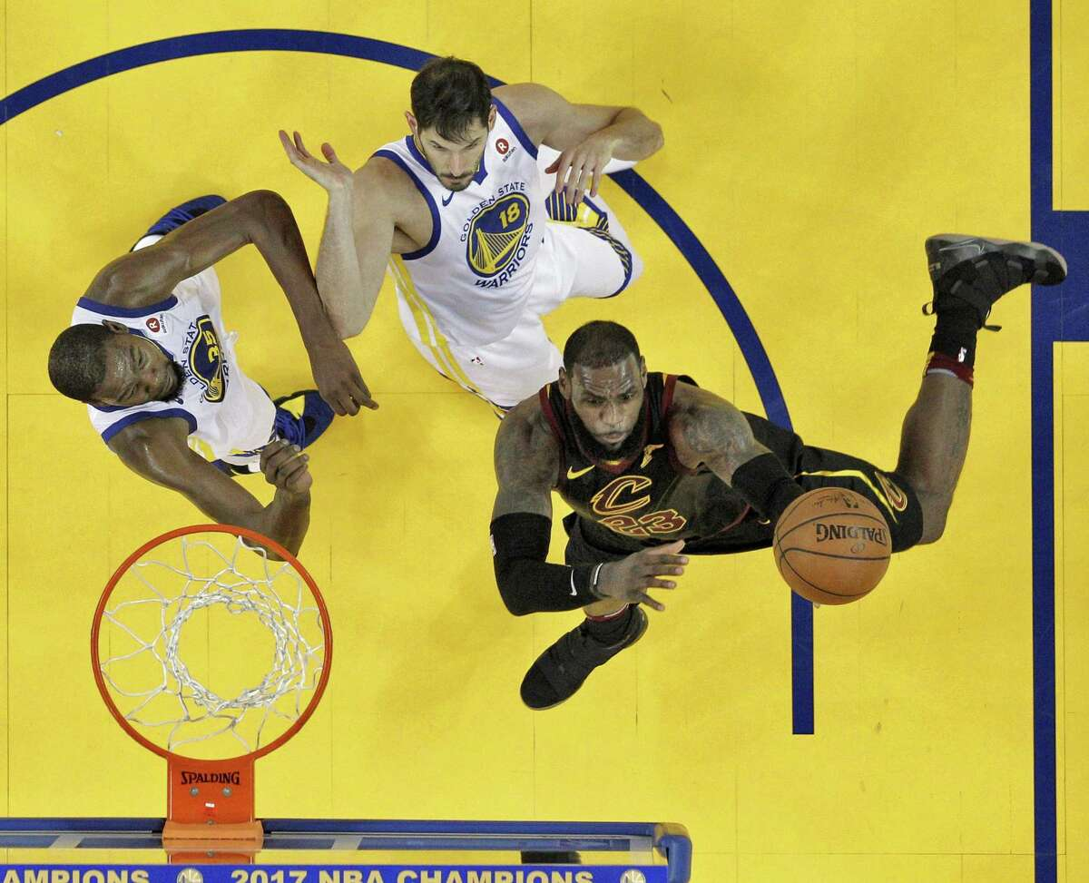 LeBron James (23) shoots while defended by Kevin Durant (35) and Omri Casspi (18) in the first half as the Golden State Warriors played the Cleveland Cavaliers at Oracle Arena in Oakland, Calif., on Monday, December 25, 2017.