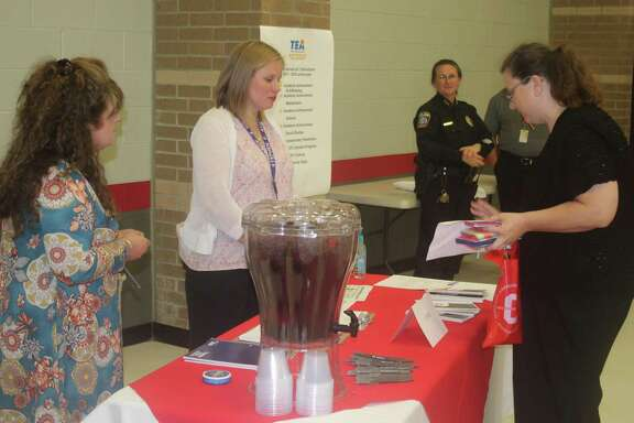 Pattie Myers (left) and Ashlee Boothe of Cleveland Middle School discuss job opportunities with a visitor to the Cleveland ISD Job Fair held on June 7 at the high school campus.