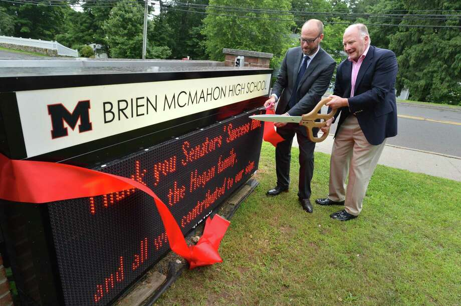 Brien McMahon High School Principal Scott Hurwitz and Jim Hogan cut the ribbon on the new electronic sign at the school during a dedication ceremony on Wednesday June 13, 2018 in Norwalk Conn. Jim's wife Leah Hogan who passed away this past fall was co-president of the parents group, Senators Success Fund that made the sign possible. Photo: Alex Von Kleydorff / Hearst Connecticut Media / Norwalk Hour