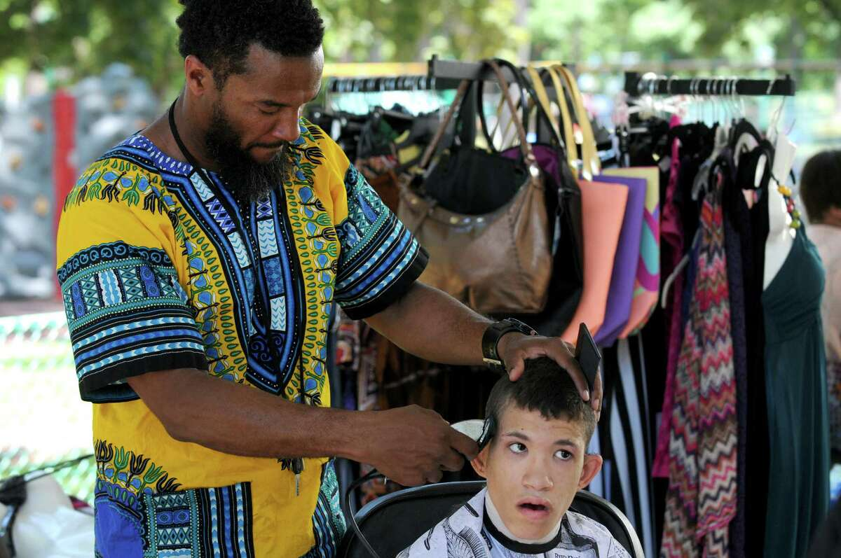 David Serra gets a fade-style cut from barber Roger Rucker of Exclusive Barber & Beauty Salon during the Hamilton Hill Arts Center-sponsored 16th Annual Juneteenth Celebration in Central Park on Saturday June 18, 2016 in Schenectady.