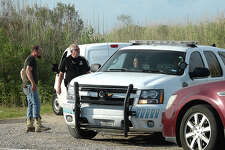 Karry McCormick talks with Port Arthur police officer as crime scene units with PAPD and Jefferson County crime lab units continued to investigate the scene located off of Texas 82 in Pleasure Island. McCormick saw the body while driving around killing time before picking up his daughter's mother from work. Photo taken Wednesday, June 13, 2018 Kim Brent/The Enterprise