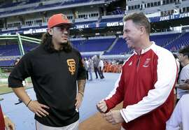 San Francisco Giants starting pitcher Dereck Rodriguez, left, talks with Tom Duffin, head baseball coach for Monsignor Edward Pace High School before a baseball game against the Miami Marlins, Wednesday, June 13, 2018, in Miami. Rodriguez, the son of former Florida Marlins catcher Ivan Rodriguez, attended school at Monsignor Edward Pace. (AP Photo/Lynne Sladky)