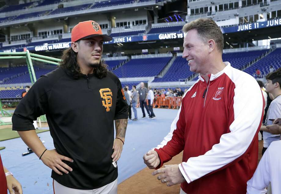 San Francisco Giants starting pitcher Dereck Rodriguez, left, talks with Tom Duffin, head baseball coach for Monsignor Edward Pace High School before a baseball game against the Miami Marlins, Wednesday, June 13, 2018, in Miami. Rodriguez, the son of former Florida Marlins catcher Ivan Rodriguez, attended school at Monsignor Edward Pace. (AP Photo/Lynne Sladky) Photo: Lynne Sladky / Associated Press