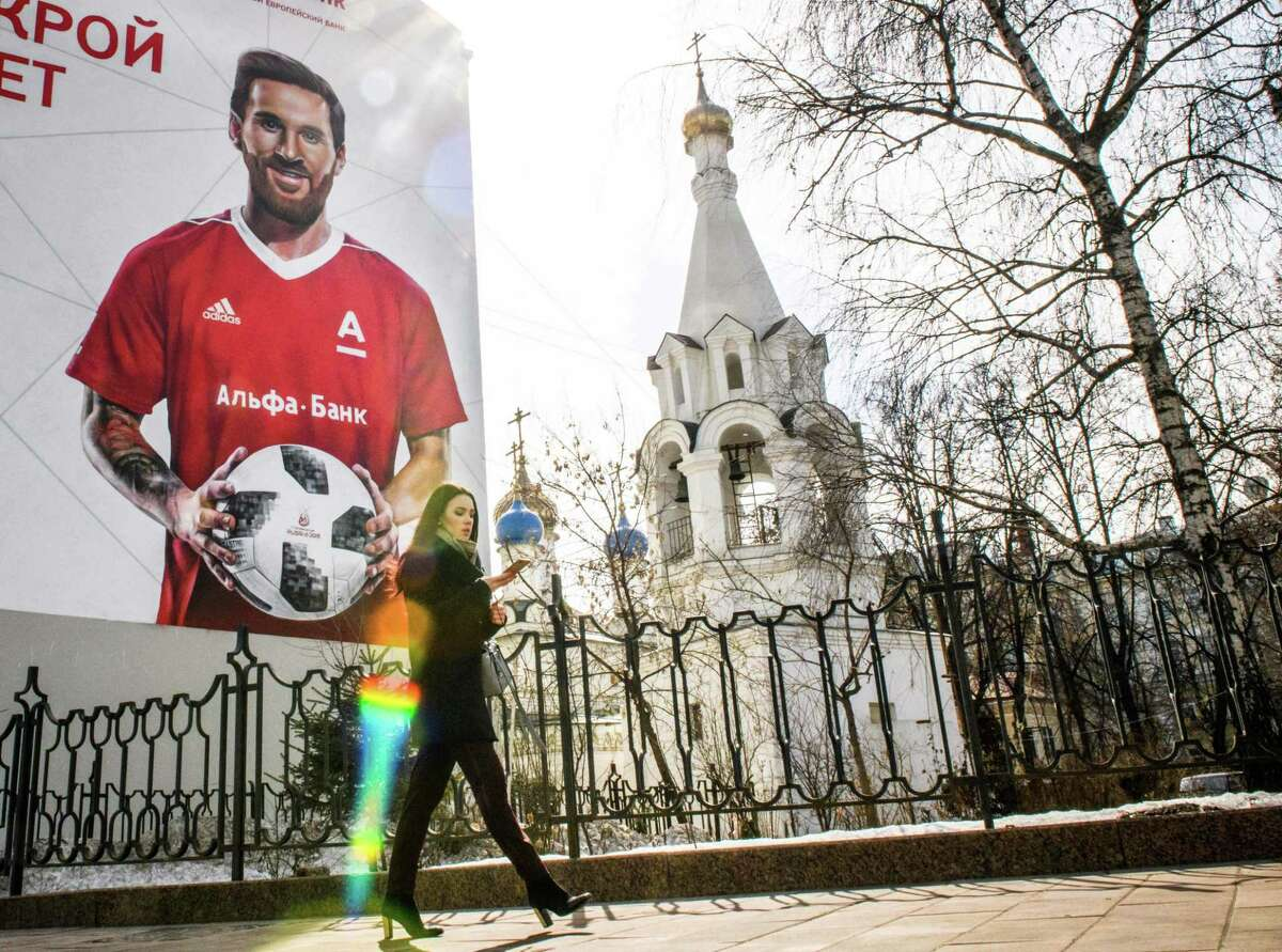 A woman walks past a wall painted with an advert for a local bank featuring Argentinian forward Lionel Messi ahead of the 2018 FIFA World Cup football tournament on April 4, 2018 in downtown Moscow. (Photo by Mladen ANTONOV / AFP) (Photo credit should read MLADEN ANTONOV/AFP/Getty Images)