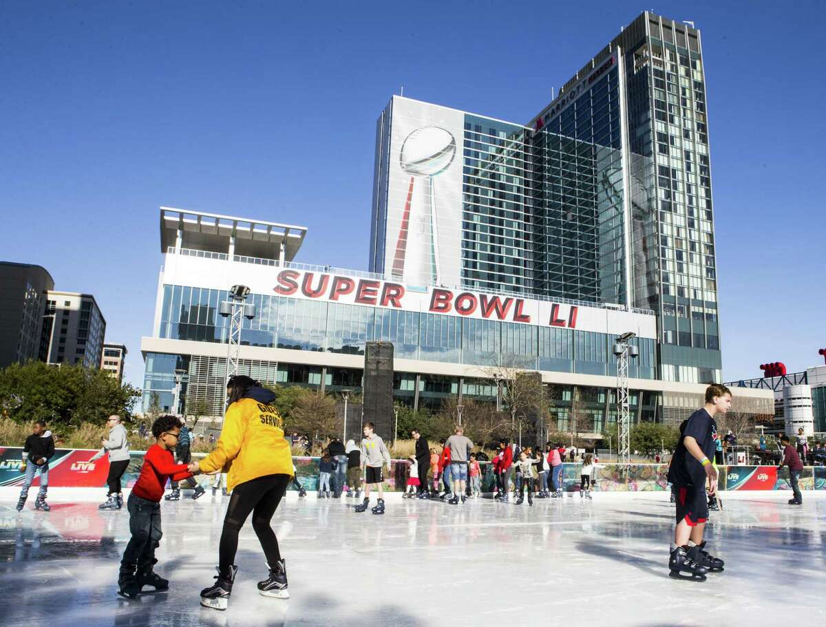 Skaters take a turn on the ice rink below a large image of the Vince Lombardi Trophy while visiting Super Bowl Live at Discovery Green on Jan. 28, 2017.