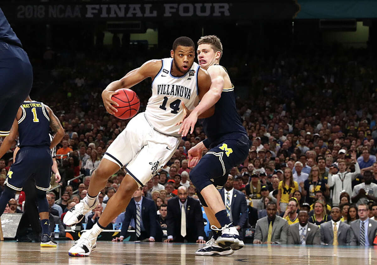SAN ANTONIO, TX - APRIL 02: Omari Spellman #14 of the Villanova Wildcats handles the ball against Moritz Wagner #13 of the Michigan Wolverines in the first half during the 2018 NCAA Men's Final Four National Championship game at the Alamodome on April 2, 2018 in San Antonio, Texas. (Photo by Tom Pennington/Getty Images)