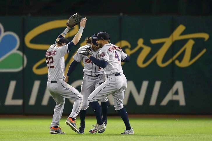 Houston Astros outfielders Josh Reddick, Jake Marisnick and George Springer, from left, celebrate the team's 6-3 win over the Oakland Athletics at the end of a baseball game Tuesday, June 12, 2018, in Oakland, Calif. (AP Photo/Ben Margot)