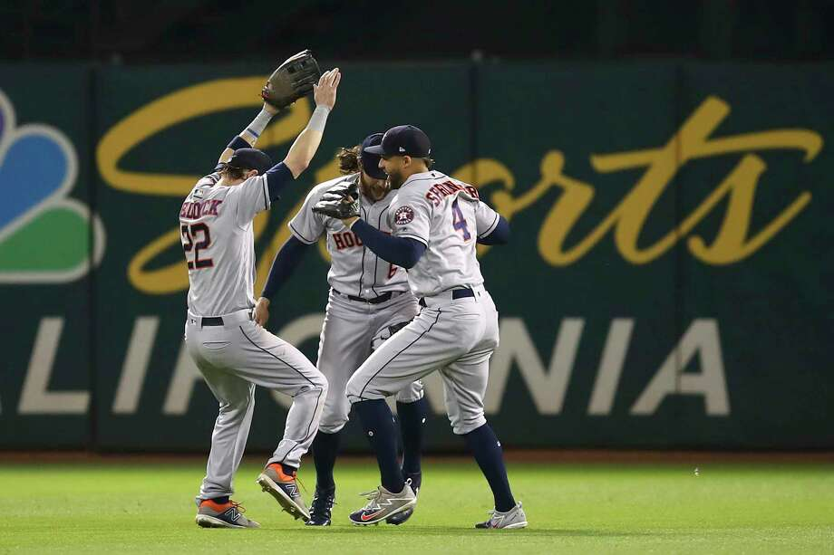 Houston Astros outfielders Josh Reddick, Jake Marisnick and George Springer, from left, celebrate the team's 6-3 win over the Oakland Athletics at the end of a baseball game Tuesday, June 12, 2018, in Oakland, Calif. (AP Photo/Ben Margot) Photo: Ben Margot, Associated Press / Copyright 2018 The Associated Press. All rights reserved.