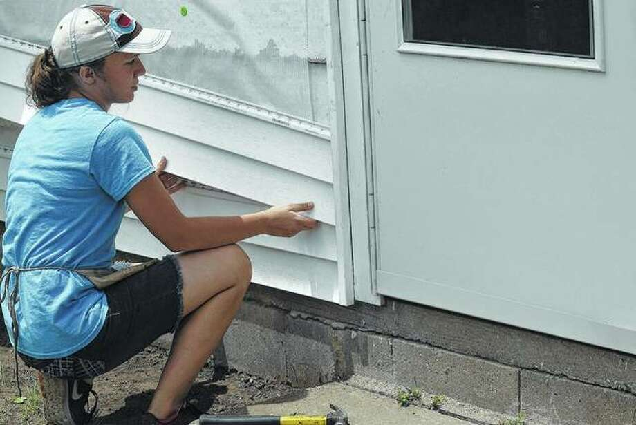 Madelynn Norton, a junior from Rushville, helps install siding on a home in Beardstown Wednesday as a part of WorkcampNE, a group of student's that help on projects for those that are not able to complete them. Photo:     Samantha McDaniel-Ogletree | Journal-Courier