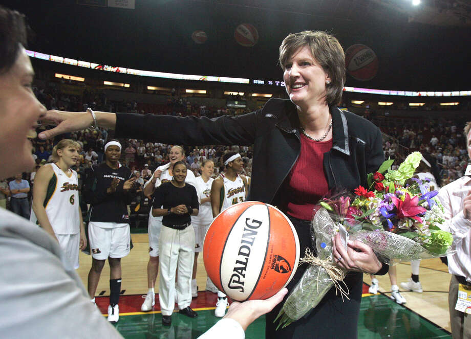 FILE - In this Aug. 19, 2005, file photo, Seattle Storm coach Anne Donovan, right, smiles as she is handed the game ball by team official Karen Bryant following the Storm's victory over the Minnesota Lyn  in Seattle. The victory gave Donovan her 100th career WNBA victory as a coach, the first woman to reach that plateau. Donovan died Wednesday, June 13, 2018, of heart failure. She was 56. Donovan's family confirmed the death in a statement. (AP Photo/Elaine Thompson, File) Photo: ELAINE THOMPSON, Associated Press / Copyright 2018 The Associated Press. All rights reserved.
