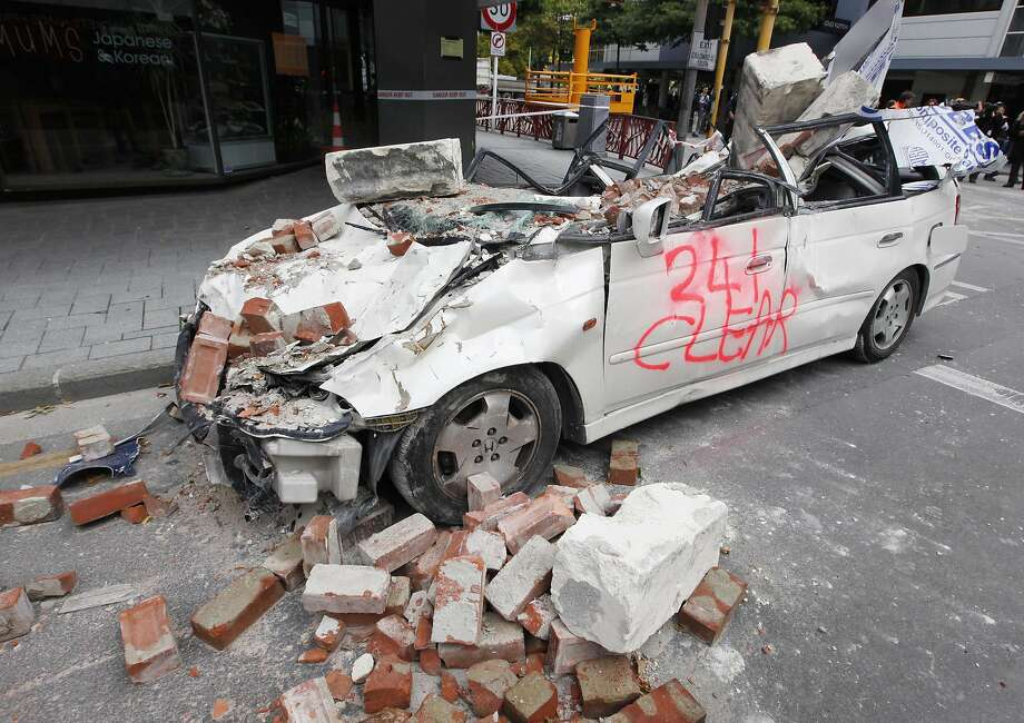 A car that was crushed by falling rubble during Tuesday's earthquake killing its occupant, sits in the central business district of Christchurch, New Zealand, Saturday, Feb. 26, 2011. Tuesday's magnitude 6.3 temblor collapsed buildings, caused extensive other damage killing more than 100 people and with 200 more missing. (AP Photo/Mark Baker) Photo: Mark Baker, AP