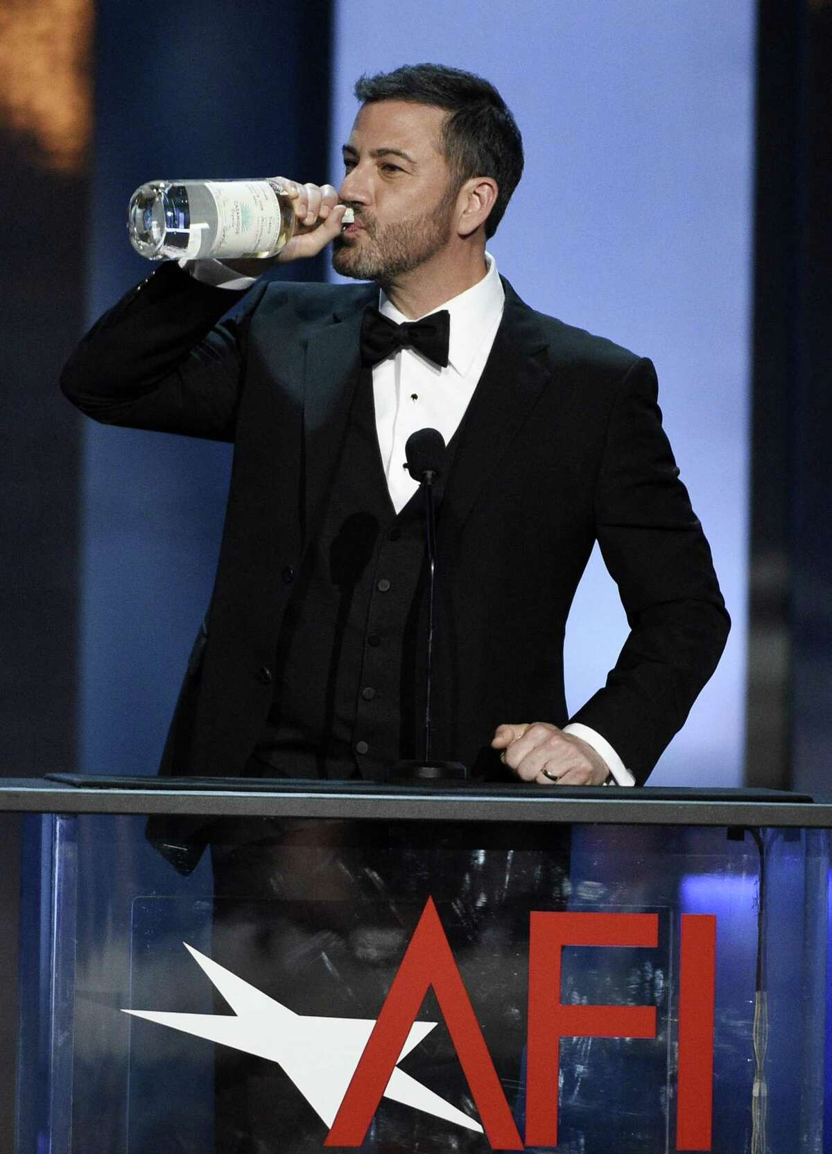 Comedian Jimmy Kimmel takes a drink from George Clooney's tequila brand Casamigos during the 46th AFI Life Achievement Award gala ceremony honoring Clooney at the Dolby Theatre, Thursday, June 7, 2018, in Los Angeles. (Photo by Chris Pizzello/Invision/AP)