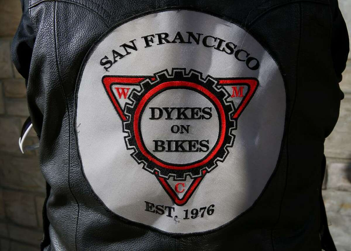 Sheila Malone, top, an emeritus member of the Dykes on Bikes who lives in the Los Angeles area, wears her vest with the motorcycle club's insignia on the back.
