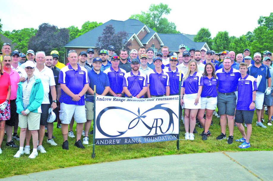 Golfers gather for a photo before the start of the Andrew Range Memorial Golf Tournament on Saturday at Fox Creek Golf Course.