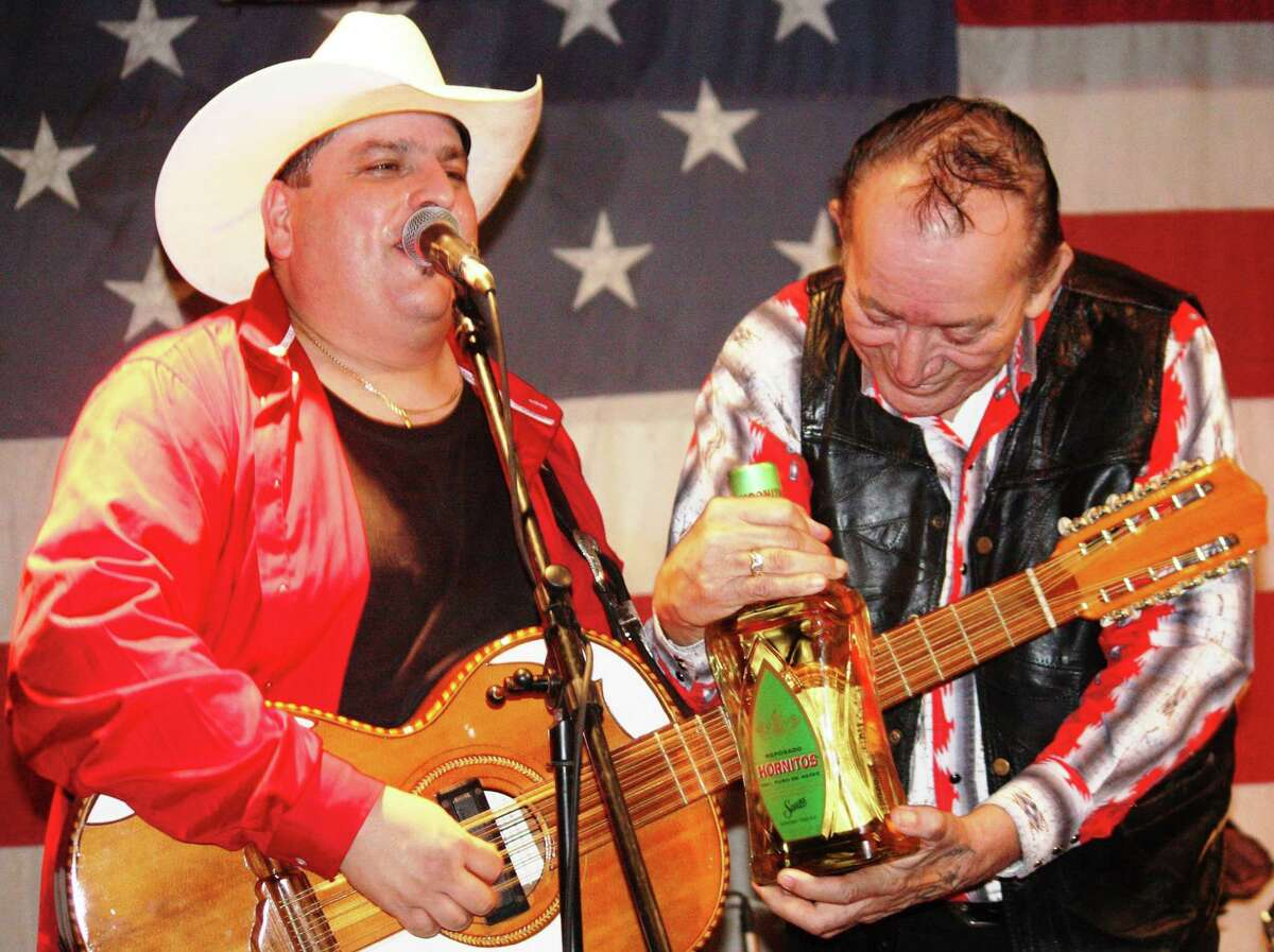 Accordion great Flaco Jimenez, right, helps Max Baca fret his bajo sexto with a tequila bottle at a 2009 Los TexManiacs show at Freiheit Country Store in New Braunfels. Baca is currently hospitalized with COVID-19.