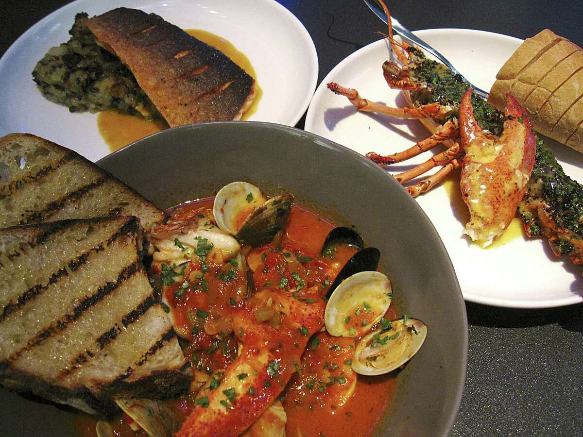 Seafood cioppino, foreground, Arctic char with Swiss chard and onion panade, left, and a grilled lobster with garlic butter and lobster claw stuffing from Rebelle