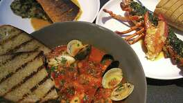 Seafood cioppino, foreground, Arctic char with Swiss chard and onion panade, left, and a grilled lobster with garlic butter and lobster claw stuffing from Rebelle.