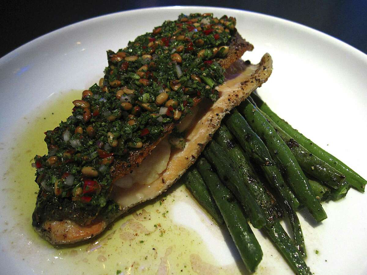 Ruby trout crusted with salsa verde, pine nuts and red Fresno chiles, stuffed with shrimp butter and served with sauteed green beans from Rebelle restaurant at the St. Anthony hotel.