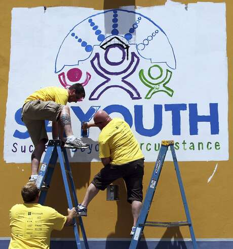 Volunteers help paint the SA Youth's Poplar Center in 2014. The non-profit has served thousands of at-risk, urban youth since the 1980s. A sale of its facility in the Beacon Hill neighborhood to the San Antonio Independent School District is pending as the district relocates offices from property it sold north and south of downtown. Photo: Bria Webb /For The Express-News / San Antonio Express-News