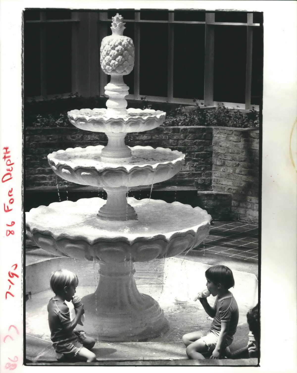May 1980: Hot day, cool kids, Matthew, 3, left, and Hands Ambrosia, 4, make the most of a hot afternoon by cooling their heels near a fountain in Northwest Mall while their mother does her shopping.