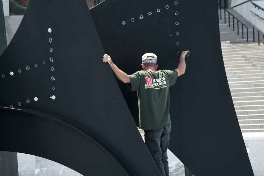 Workers dismantle and temporary remove artist Alexander CalderÕs abstract sculpture Triangles and Arches from the reflecting pool in front of the grand staircase on the south end of the Empire State Plaza on Thursday, June 14, 2018 in Albany, N.Y. (Lori Van Buren/Times Union) Photo: Lori Van Buren, Albany Times Union / 20043958A