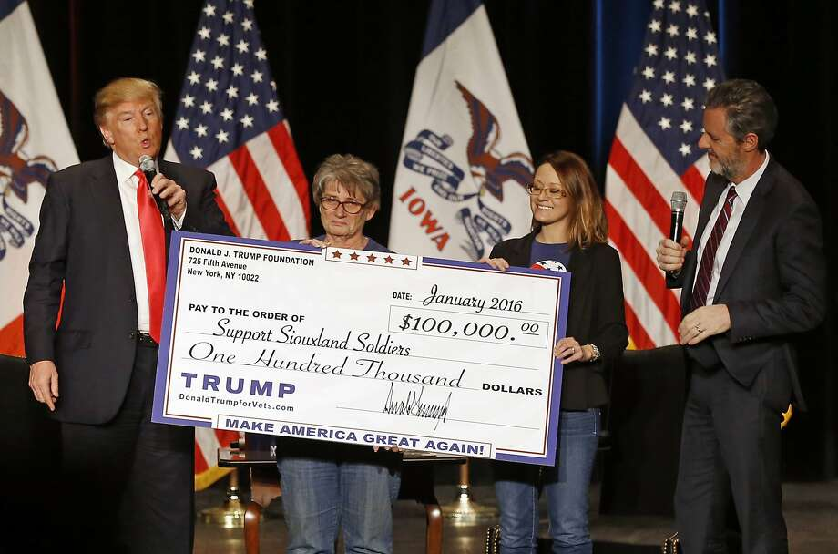 FILE - In this Jan. 31, 2016 file photo, Donald Trump, left, stages a check presentation with an enlarged copy of a $100,000 contribution from the Donald J. Trump Foundation to Support Siouxland Soldiers during a campaign event in Sioux City, Iowa., during Trump's run for president. New York Attorney General Barbara Underwood filed a lawsuit Thursday June 14, 2018, accusing Trump of illegally using his charitable foundation to pay legal settlements related to his golf clubs and to bolster his presidential campaign with Foundation disbursements such as this one in Iowa. Also pictured is Jerry Falwell, Jr., right, president of Liberty University. (AP Photo/Patrick Semansky, File) Photo: Patrick Semansky, Associated Press