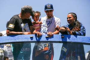 Stephen Curry's family Dell Curry (left) and his wife Ayesha Curry (right) join him while he holds his daughter Ryan Curry during the Warriors Championship Parade in Oakland, California, on Tuesday, June 12, 2018.