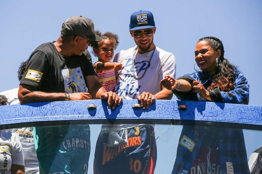 Stephen Curry's family Dell Curry (left) and his wife Ayesha Curry (right) join him while he holds his daughter Ryan Curry during the Warriors Championship Parade in Oakland, California, on Tuesday, June 12, 2018. Photo: Gabrielle Lurie / The Chronicle