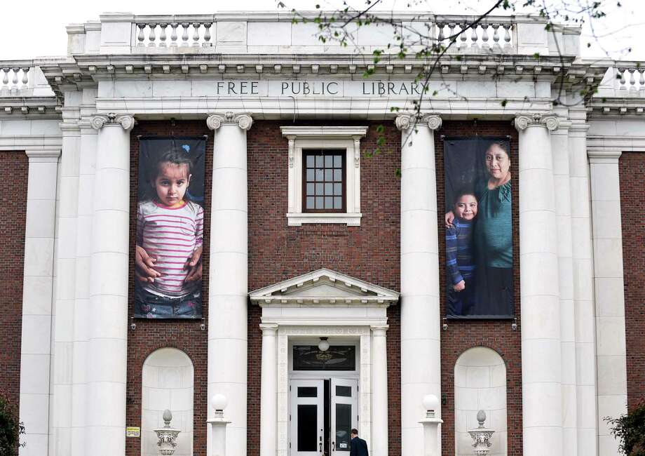 Photographs of immigrants hang in the front of the New Haven Free Public Library. Photo: Arnold Gold / Hearst Connecticut Media / New Haven Register
