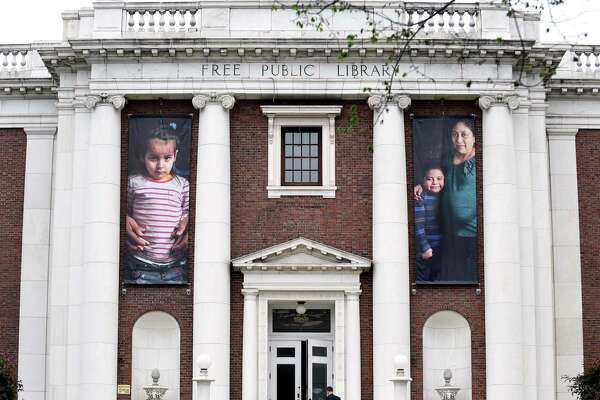 Photographs of immigrants hang in the front of the New Haven Free Public Library.