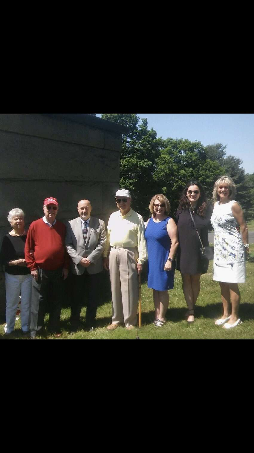 Troy Mayor Patrick Madden (third from left) joins descendants of Troy hero Jack J. Callahan at the grave of the Troy High alum who was action at age 18. Callahan's grand neice, Lisa Karam (in blue dress, third from right) and husband Jim Karam researched the last day of Callahan's brave life. (Family photo)