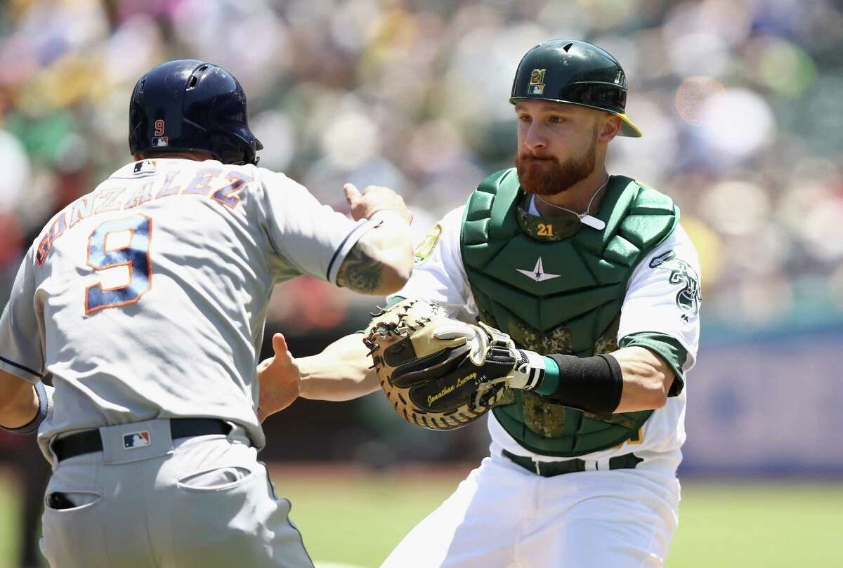 OAKLAND, CA - JUNE 14: Jonathan Lucroy #21 of the Oakland Athletics tags out Marwin Gonzalez #9 of the Houston Astros in a rundown in the second inning at Oakland Alameda Coliseum on June 14, 2018 in Oakland, California.