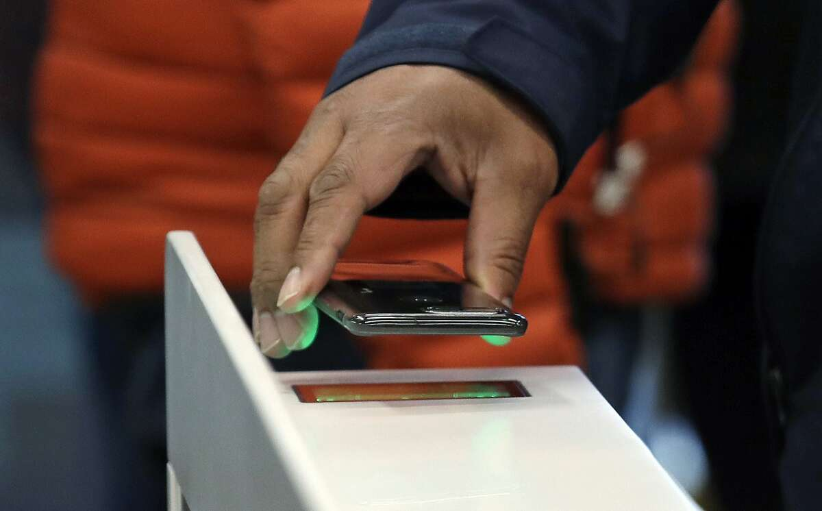 FILE- In this Jan. 22, 2018, file photo a shopper scans an Amazon Go app on a cellphone while entering an Amazon Go store in Seattle. Microsoft is working on automated checkout technology that could help retailers compete with Amazon's new cashier-less stores. (AP Photo/Elaine Thompson, File)