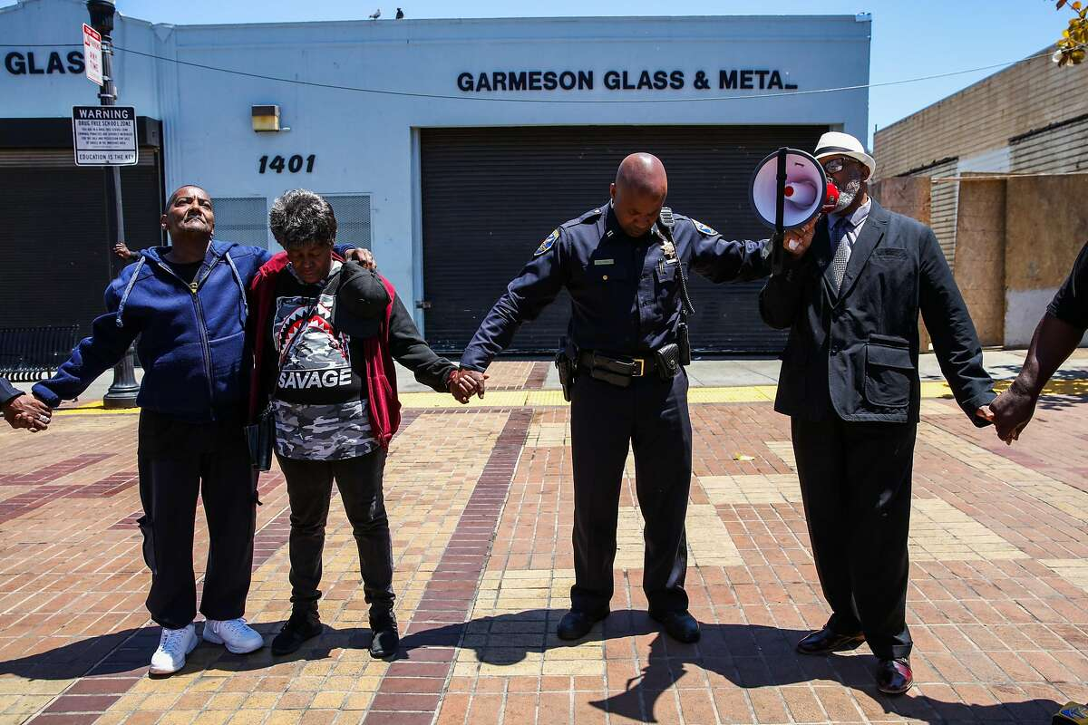 Bishop Ishmael Burch (right) speaks during a prayer as he stands next to Lorenzo Cael Sr. (left) and Wanda Fain (second from left), the parents of Jevon Cael who was shot and killed last week in the Bayview in San Francisco, California, on Monday, June 11, 2018.